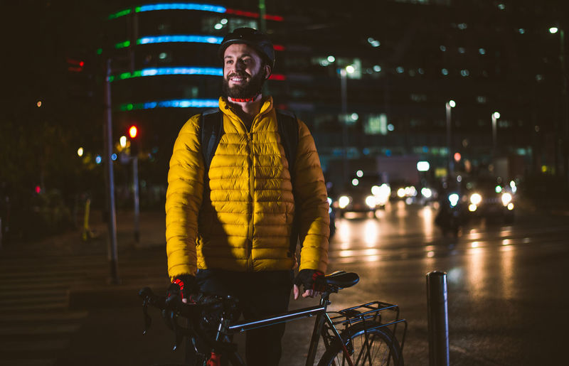 Man standing with bicycle on street in city at night