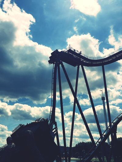 Silhouette Of Rollercoaster Rides Against Cloudy Sky