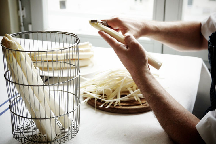 Cropped Hands Cutting White Asparagus At Home