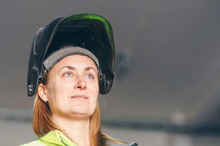 Female worker wearing welding mask