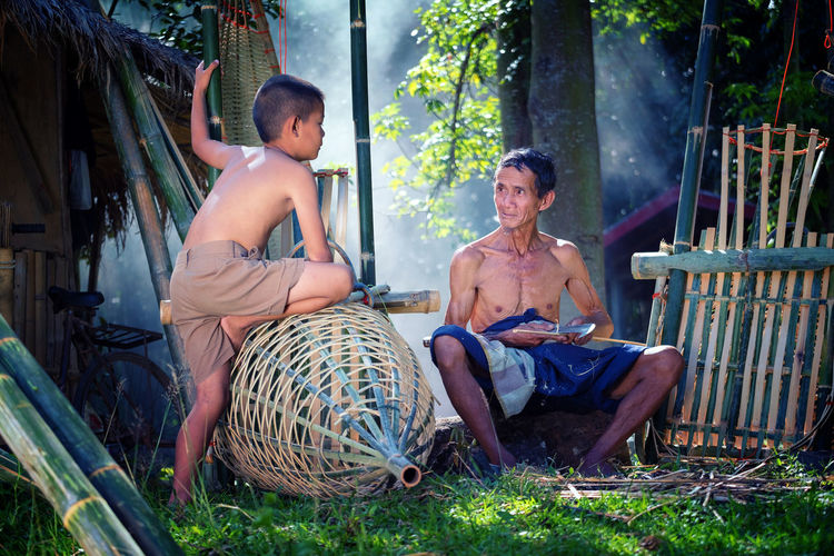 Boy Talking With Father Sitting On Field