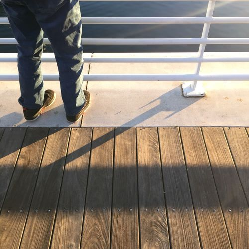 Low section of man standing on pier