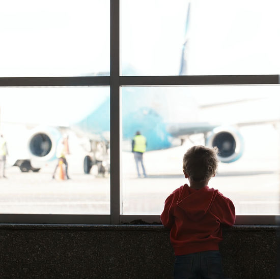 Rear view of boy looking through window at airport terminal