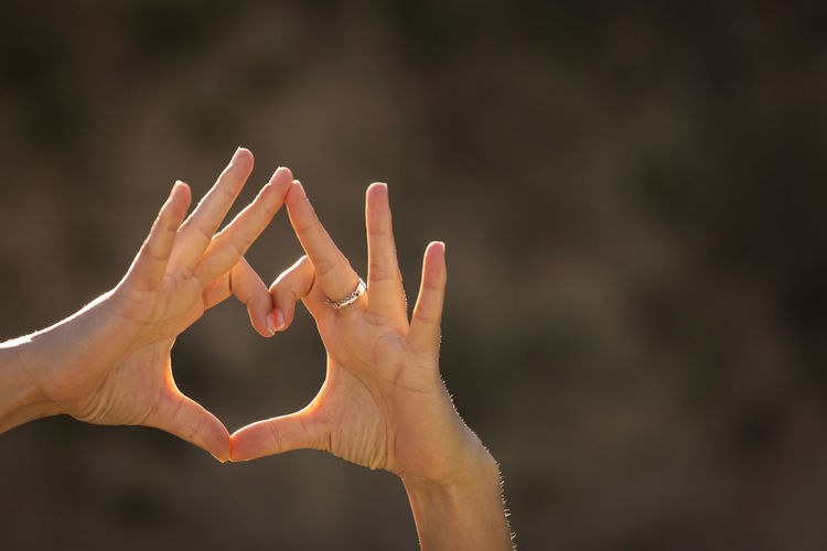 Close-up of hands gesturing heart shape