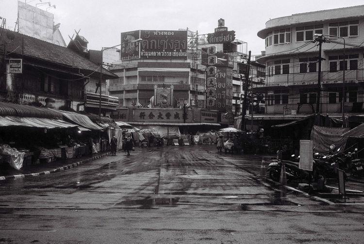 Street amidst buildings in city during rainy season