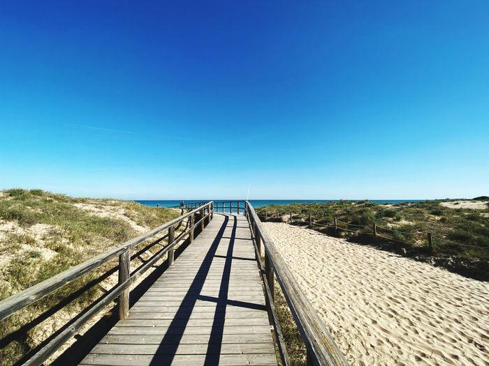 View of wooden footbridge against clear blue sky