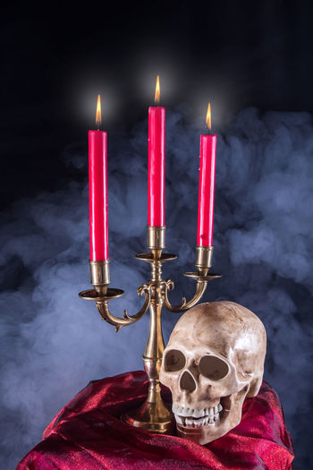 an eerie altar with candles and a skull Altar Ritual Belief Black Background Burning Candle Celebration Close-up Fire Fire - Natural Phenomenon Flame Fog Human Body Part Human Bone Human Skeleton Human Skull Illuminated Indoors  Red Religion Scary Spirituality Spooky Superstition