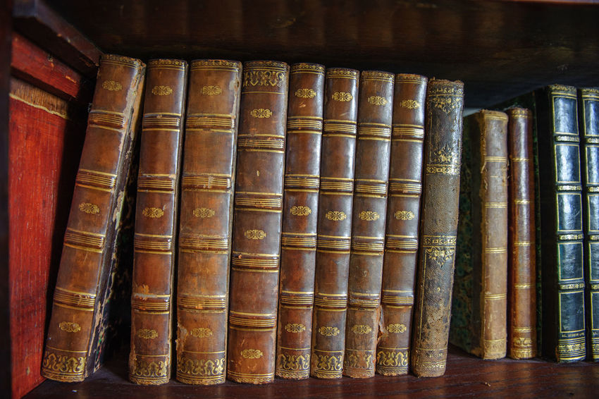 Old books on the wooden bookshelf Antique Vintage Books Ancient History Book Book Cover Bookshelf Close-up Education Hardcover Book History Library Literature Old Old-fashioned Vintage Wisdom