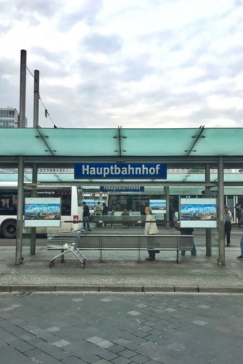 Man standing at bus stop against sky