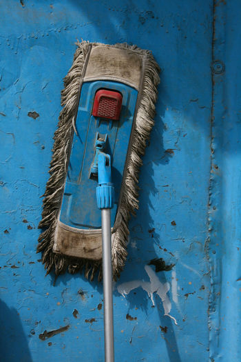 Abandoned mop against blue wall