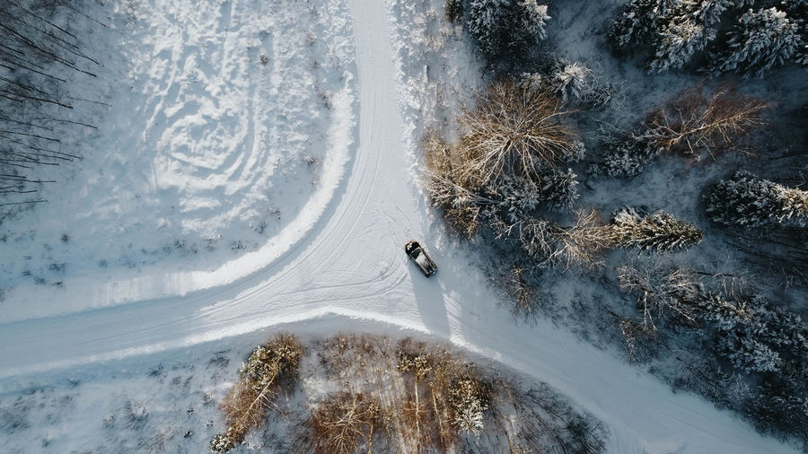 Aerial view of forest in winter mountain. three to four roads with car in the middle. estonia.