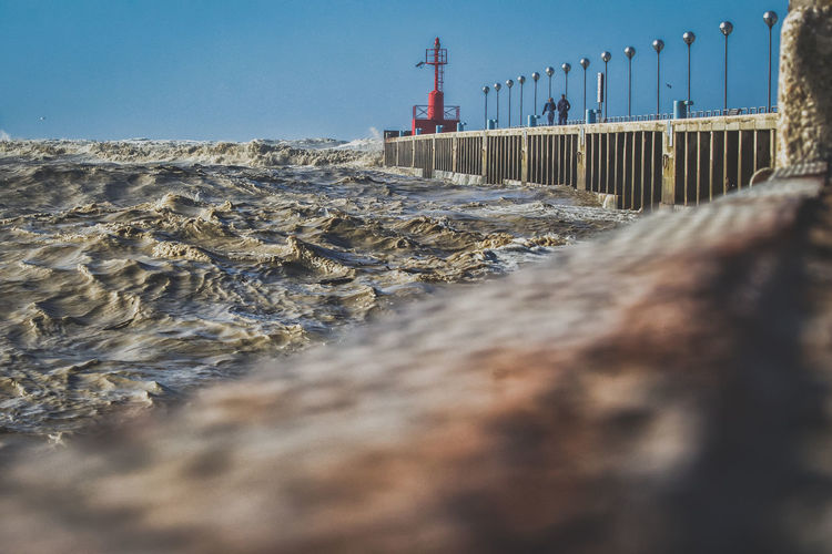 View of sea waves crashing at pier against sky