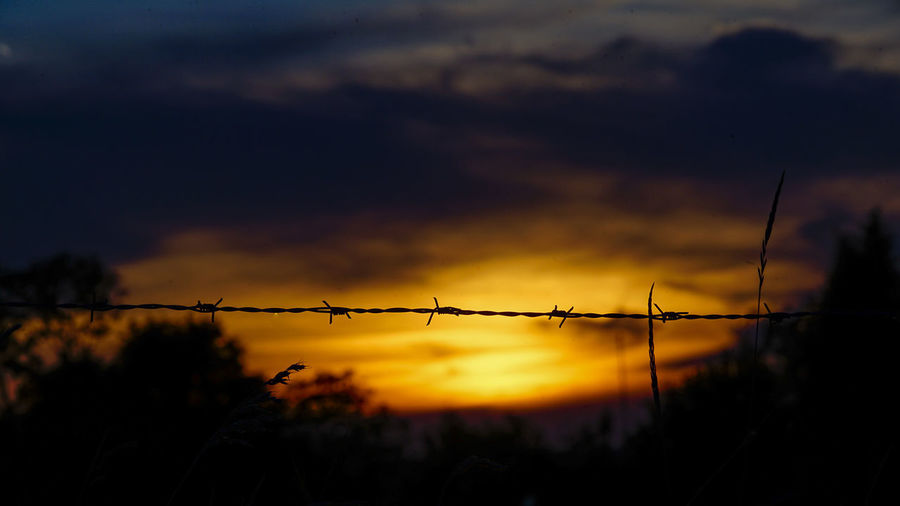 Silhouette of barbed wire against sky during sunset