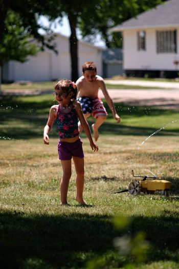 Full length of children playing on grassy field at backyard