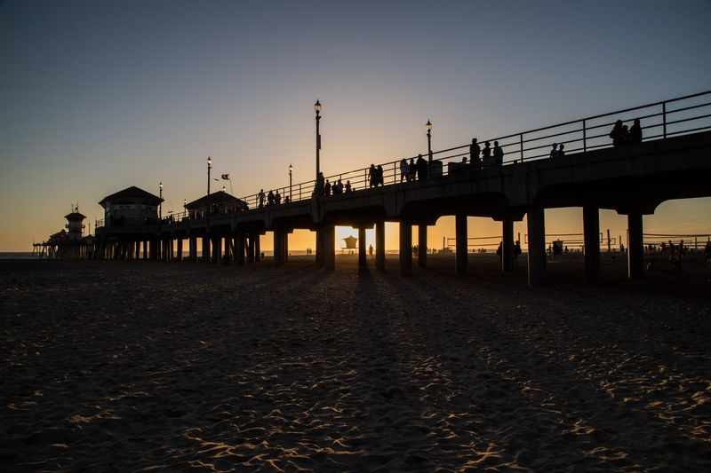 Silhouette people on pier at huntington beach against sky during sunset