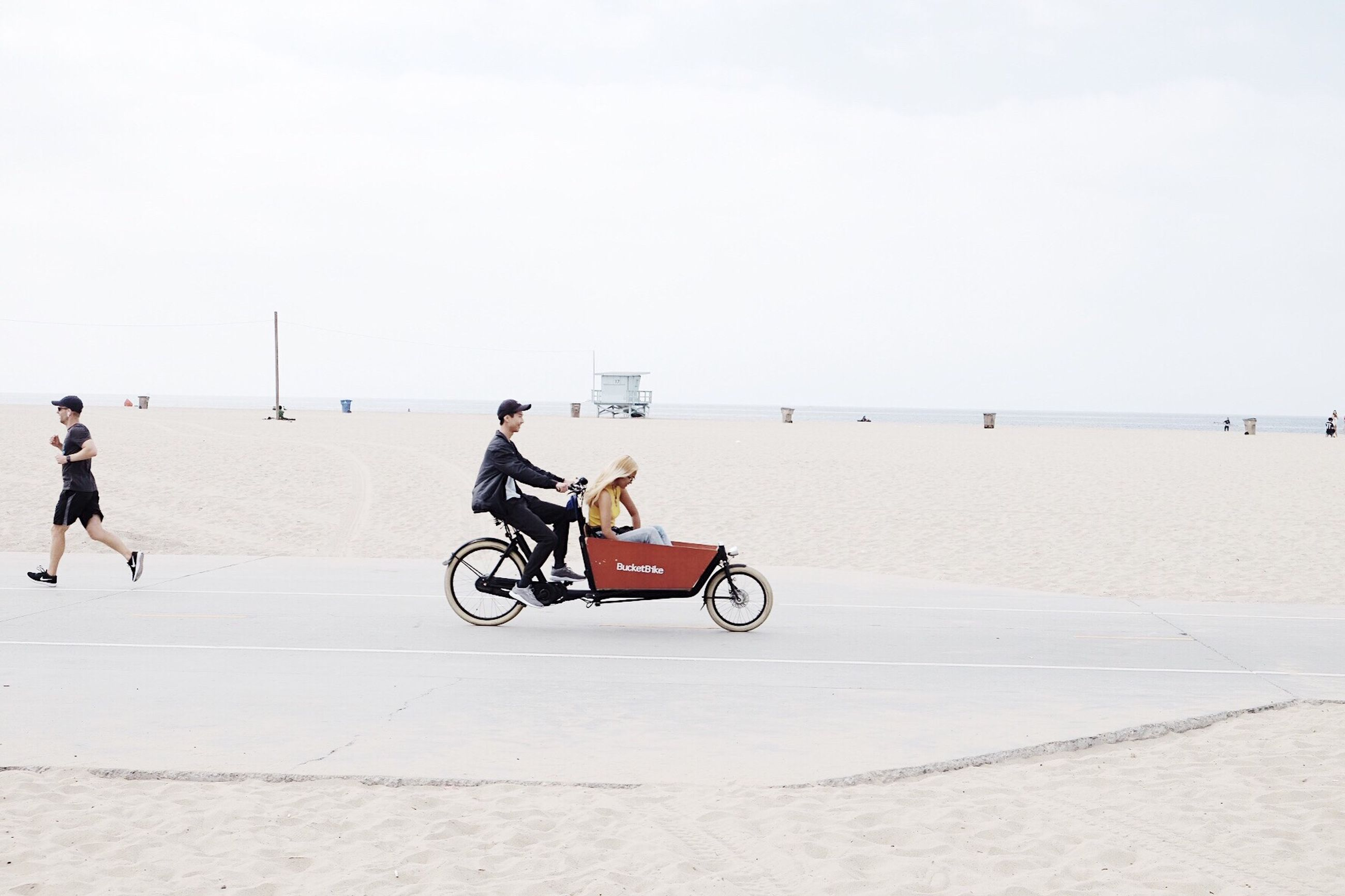 transportation, full length, day, copy space, outdoors, sea, beach, riding, clear sky, sky, sand, land vehicle, real people, men, sitting, horizon over water, nature, water, one person, young adult, people