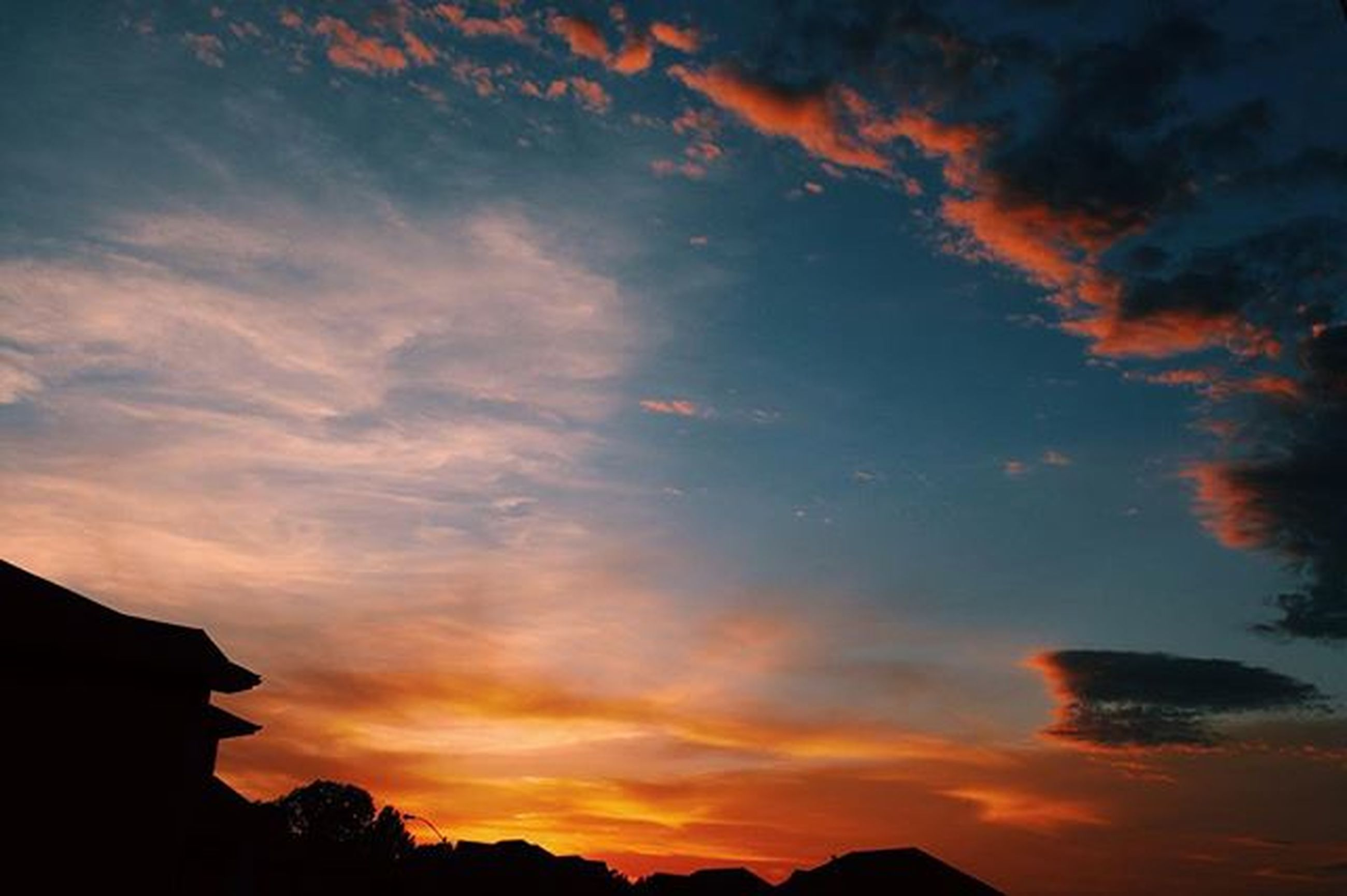 sunset, sky, silhouette, orange color, cloud - sky, beauty in nature, scenics, dramatic sky, tranquil scene, tranquility, nature, cloud, cloudy, low angle view, idyllic, building exterior, moody sky, majestic, weather, built structure