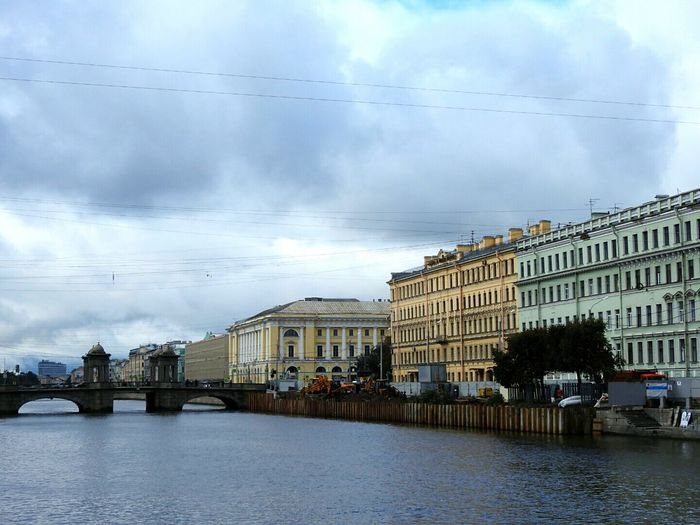 View of canal with bridge in city against cloudy sky