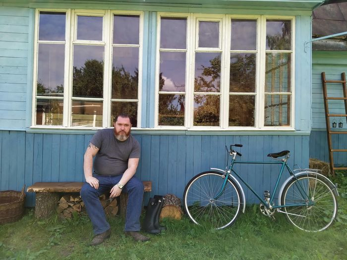 Full length portrait of smiling man on bicycle against building