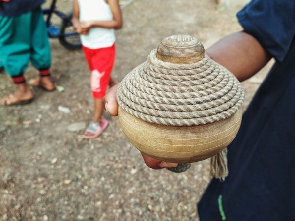 Top Spinner Childhood Playing Wood - Material Traditional Play Traditional Culture Real People Men Low Section Day Outdoors Human Leg Lifestyles Human Body Part People Close-up Human Hand