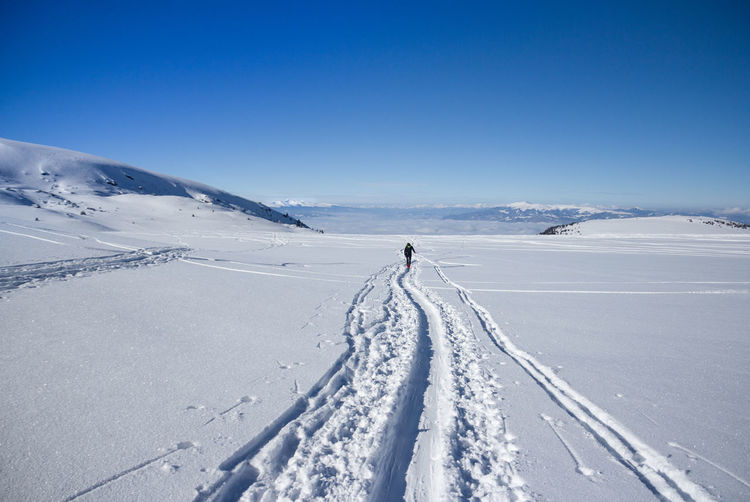 Person on snow covered field against sky
