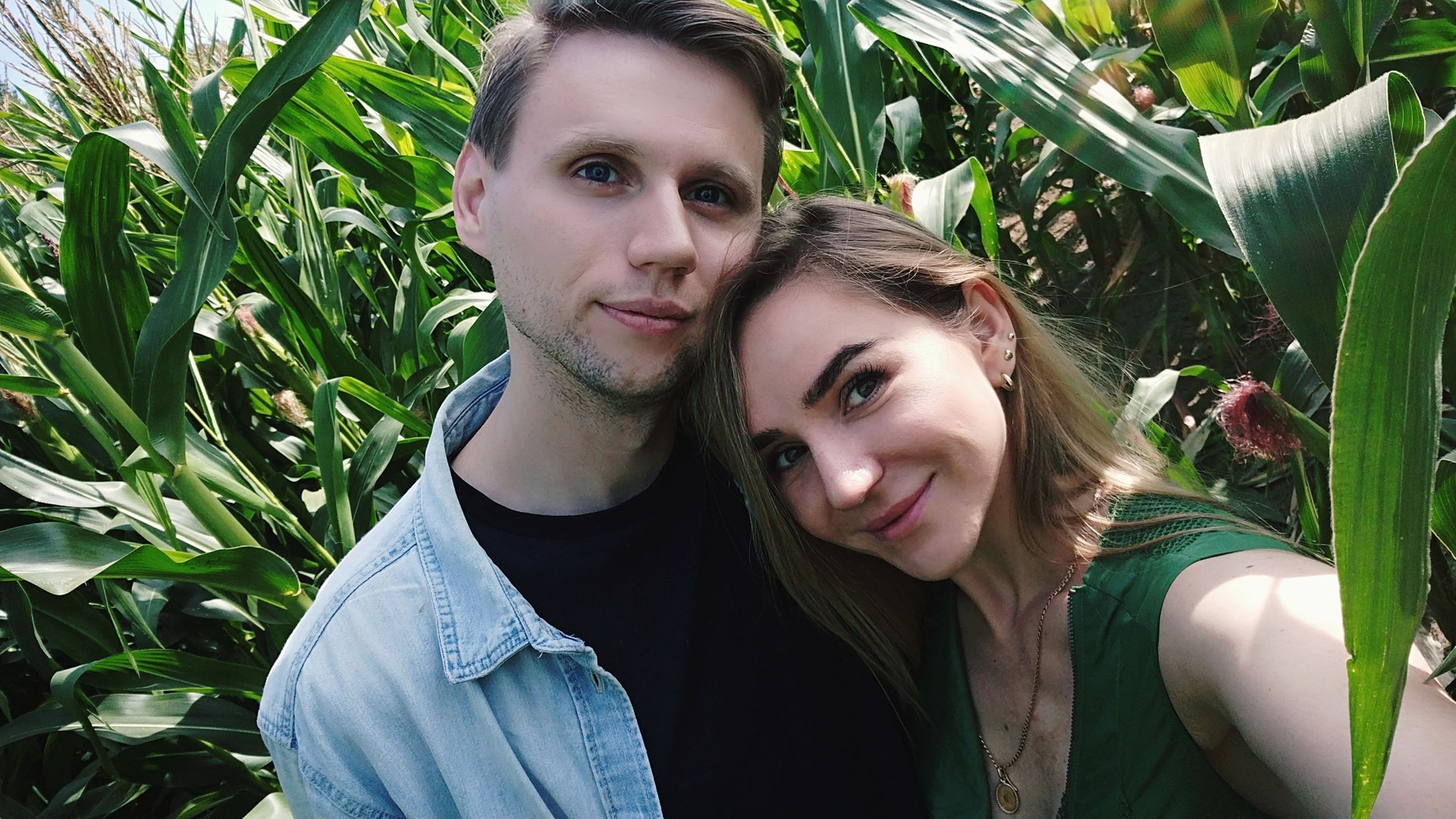 portrait, two people, looking at camera, young adult, young women, plant, smiling, adult, lifestyles, leisure activity, emotion, bonding, headshot, togetherness, young men, women, front view, real people, couple - relationship, positive emotion, beautiful woman, outdoors