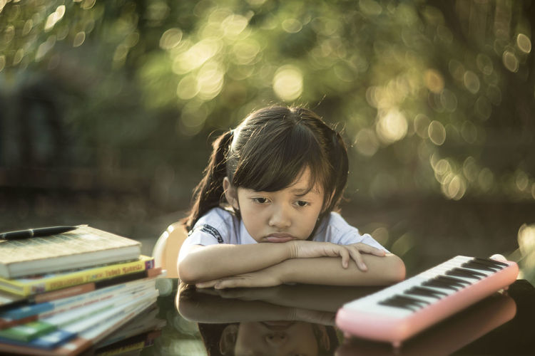 A little girl studying wearing a school uniform at the outdoor class with glimmering background in the morning light Book Childhood Children Only Day Education Indoors  Learning Music One Person People Real People Sitting