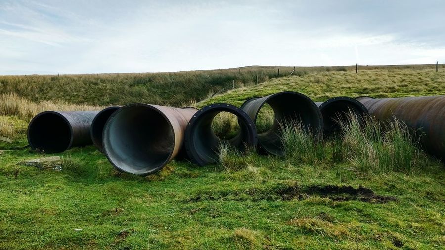Pipes on field against sky