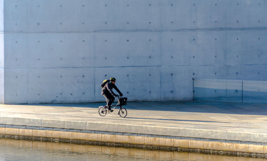 Mature man riding bicycle on street by river