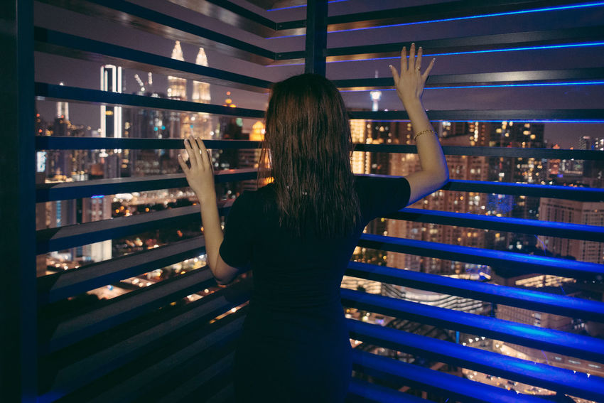 One Person Standing Rear View Long Hair Hairstyle Lifestyles Real People Illuminated Indoors  Adult Women Night Waist Up Hair Casual Clothing Leisure Activity Brown Hair Three Quarter Length Arms Raised Human Arm City Lights Cityscape