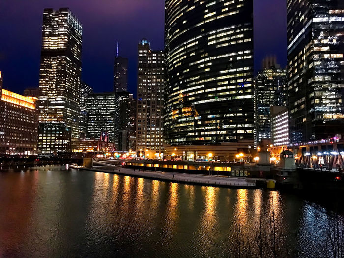 Chicago's colorful cityscape reflecting onto a nearly frozen river in winter. Chicago Chicago River Chicago Loop Cityscape Downtown Chicago Reflection Rush Hour Skyscrapers Winter Architecture Building Exterior Building Exterior Architecture Built Structure City Cold Temperature Colorful Downtown District Modern Outdoors Pedestrian Riverwalk Sky Tower Travel Destinations Urban Skyline