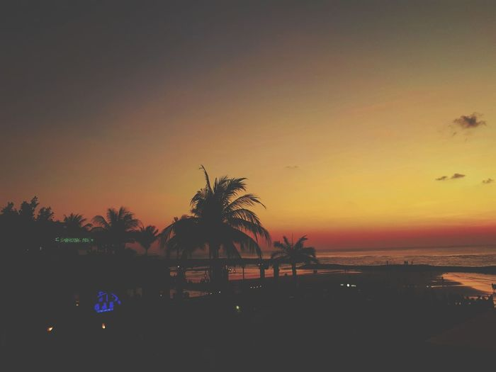 Silhouette palm trees by sea against romantic sky at sunset