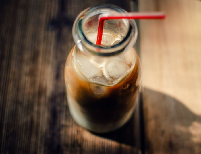 Close-up of iced coffee in glass bottle with straw on table