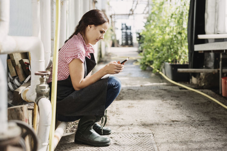 Young woman using mobile phone while sitting outdoors