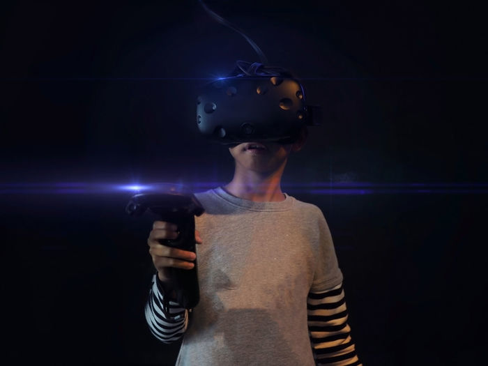 Young asian boy holding and wearing vr game set in the black background. selected focus.