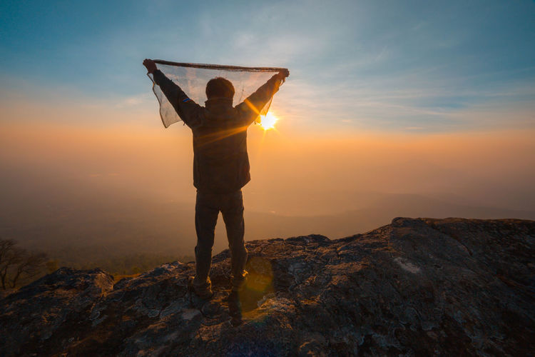 freedom man on mountain with sunrise Freedom Hiking Arms Raised Beauty In Nature Concept Day Full Length Hand Raised Hiker Landscape Lifestyles Mountain Nature One Person Orange Color Outdoors People Real People Rock - Object Scenics Sky Standing Success Sun Sunset Tranquil Scene Tranquility Women