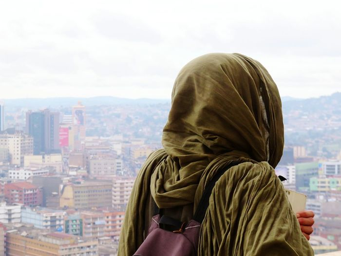 Rear view of woman wearing headscarf looking at view in city against sky
