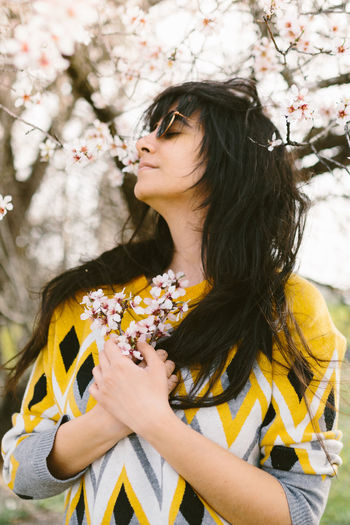 Midsection of woman with yellow flowers
