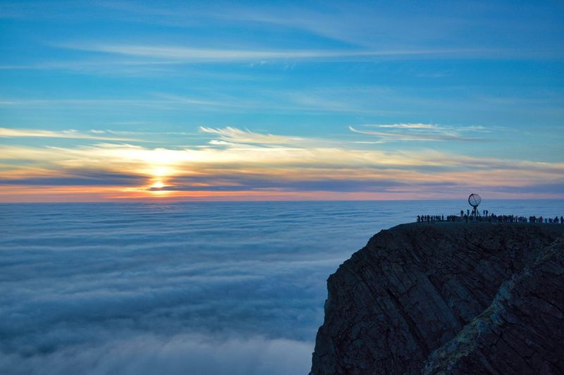 Midnight sun 'sunset' photo from the famous Nordkapp cliff landmark location, in July. End Of Europe Midnight Sun Midnight Sunset Blue Sky And Clouds Cliff Cloud - Sky End Of The World Horizon Over Water Landmark Leisure Activity Lifestyles Monument Nature Nordkapp Outdoors People Scenics Sea Sea Fog Silhouette Sky Sunset Tranquil Scene Tranquility Water