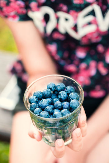 Girl holding glass filled with fresh blueberries. Girl wearing flowery red blouse sunglasses and sitting on bench in the garden Berries Dessert Eating Freshness Life Woman Young Berry Blueberries Blueberry Enjoying Enjoyment Female Food Fresh Fruit Garden Girl Healthy Joy Organic Outdoors person Summer Sweet
