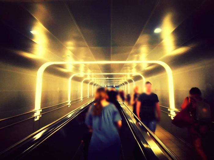 Blurred motion of people walking in illuminated tunnel