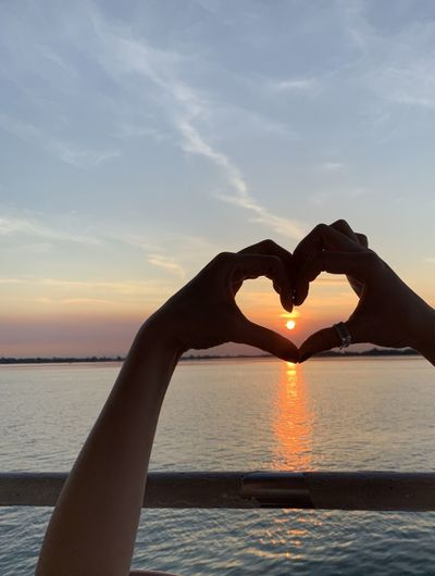 Person hand holding heart shape against sea during sunset