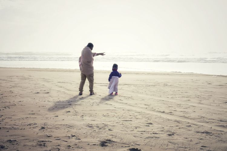 Father and daughter standing on bright beach