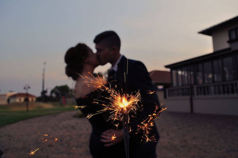 Couple kissing by lit sparkler in city