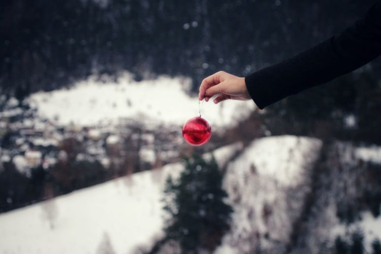 Cropped Hand Holding Red Bauble During Winter
