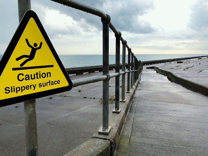 Caution! Cloud - Sky Sky Water Sign Communication Text Day Sea Railing Warning Sign Safety Outdoors Horizon Over Water No People Wet