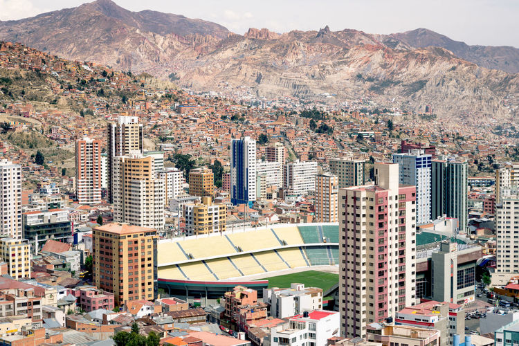 Stadium amidst buildings by mountains
