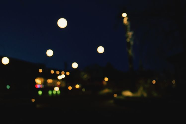 Defocused image of illuminated street lights in city at night