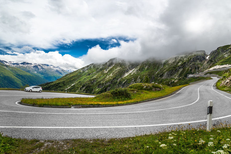 Road Leading Towards Majestic Mountains Against Cloudy Sky