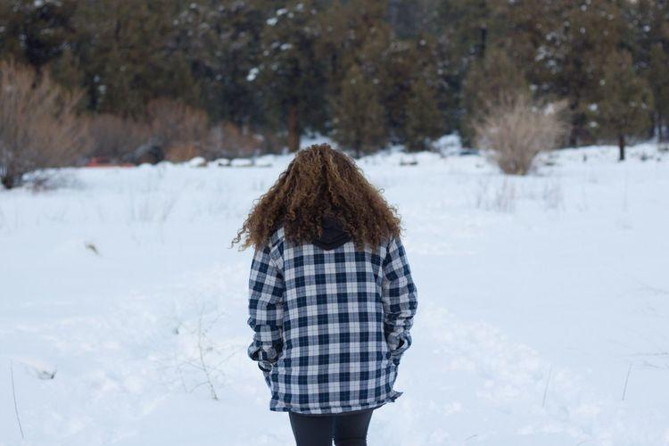 Rear view of woman walking on snow field